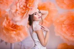Stående av den unga härliga flickan i pappers- blommor Arkivfoto