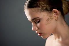 Stående av den unga härliga flickan i studio, med yrkesmässig makeup Skönhetskytte På framsidamodellgulden som besprutas royaltyfri bild