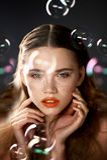 Stående av den unga härliga flickan i studio, med yrkesmässig makeup Skönhetskytte Skönheten av såpbubblor _ fotografering för bildbyråer