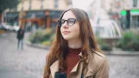 Stående av den unga härliga franska studenten i exponeringsglas som står på gatan, drinkte från locket och ler på kameran stock video