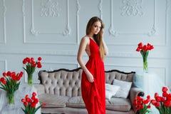 Stående av den unga härliga kvinnan i röd klänning med tulpan i lyxig inre Royaltyfri Fotografi
