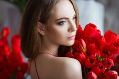 Stående av den unga härliga kvinnan i röd klänning med tulpan i lyxig inre Arkivbild