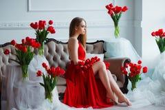 Stående av den unga härliga kvinnan i röd klänning med tulpan i lyxig inre Royaltyfria Foton