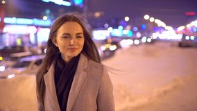 Stående av den unga härliga kvinnan i staden vid gatan Unga härliga kvinnor som går på natten i staden som ler och lager videofilmer