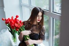 Stående av den unga härliga kvinnan i svart klänning med tulpan i lyxig inre Fotografering för Bildbyråer