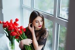 Stående av den unga härliga kvinnan i svart klänning med tulpan i lyxig inre Royaltyfria Bilder
