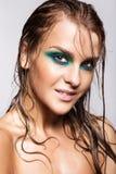 Stående av den unga härliga kvinnan med våt glänsande makeup för gräsplan Royaltyfri Foto
