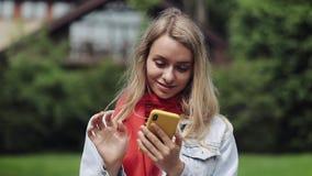 Stående av den unga härliga kvinnan som använder appen på smartphonen, ler och smsar på mobiltelefonen Kvinna som bär i det rött stock video