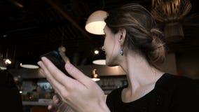Stående av den unga härliga kvinnan som arbetar i kafé Brunettkvinnlig som använder smartphonen för att surfa internet stock video