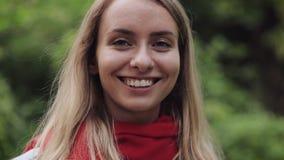 Stående av den unga härliga kvinnan som bär den röda halsduken som inhalerar och utandas ny luft och att ta djup andedräkt som fö stock video