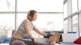 Stående av den unga härliga unga kvinnan som gör yoga- eller pilatesövning lager videofilmer