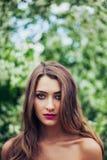 Stående av den unga härliga kvinnan som poserar bland vårblomningträd Fotografering för Bildbyråer