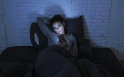 Stående av den unga härliga latinska kvinnan som sent använder ligga för natt för mobiltelefon - sömnlöst i säng i mörkret i smar Arkivfoton