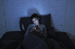 Stående av den unga härliga latinska kvinnan som sent använder ligga för natt för mobiltelefon - sömnlöst i säng i mörkret i smar Royaltyfri Fotografi