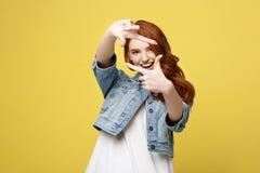 Stående av den unga härliga ljust rödbrun kvinnan med fräknar som ler cheerfuly göra en kameraram med fingrar Isolerat på arkivbilder