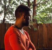 Stående av den unga härliga mannen i apelsin, mot utomhus- bakgrund Royaltyfria Bilder