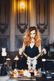 Stående av den unga härliga rödhåriga flickan i bilden av en gotisk häxa på allhelgonaafton Arkivfoto