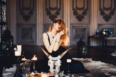 Stående av den unga härliga rödhåriga flickan i bilden av en gotisk häxa på allhelgonaafton Arkivfoton