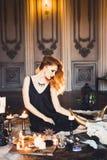 Stående av den unga härliga rödhåriga flickan i bilden av en gotisk häxa på allhelgonaafton Royaltyfria Bilder