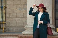 Stående av den unga härliga trendiga kvinnan som poserar på gatan Dam som bär den stilfulla röda hatten och handväskan, smaragd arkivbild