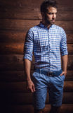Stående av den unga härliga trendiga mannen mot träväggen arkivfoto