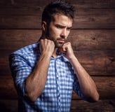 Stående av den unga härliga trendiga mannen mot träväggen royaltyfri fotografi