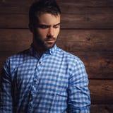 Stående av den unga härliga trendiga mannen mot träväggen fotografering för bildbyråer