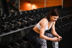 Stående av den unga idrottskvinnan med smartphonen som lyssnar till musik i idrottshall arkivfoton