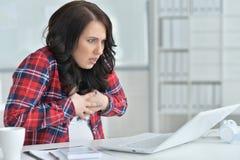 Stående av den unga ilskna affärskvinnan som i regeringsställning arbetar med bärbara datorn arkivfoton