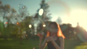 Stående av den unga kvinnan för härlig redhair Blåsa bubblan i parkera arkivfilmer
