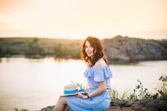 Stående av den unga kvinnan i blå romantisk klänning med hatten som sitter nära floden och tycker om solnedgångafton Stillhet och royaltyfri bild