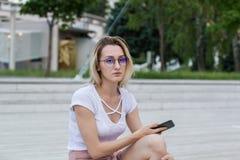 Stående av den unga kvinnan i glasögon som utomhus rymmer telefonen i parkera Fotografering för Bildbyråer