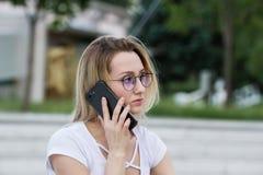 Stående av den unga kvinnan i glasögon som utomhus talar på telefonen Royaltyfria Bilder