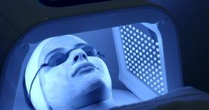 Stående av den unga kvinnan i maskering och exponeringsglas som mottar den ansikts- skönhetbehandlingen av ledd ljus terapi i bru stock video