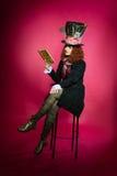 Stående av den unga kvinnan i similituden av hattmakareläsningen Fotografering för Bildbyråer