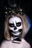 Stående av den unga kvinnan med förskräckt halloween makeup över svart bakgrund Royaltyfri Foto