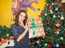 Stående av den unga kvinnan med gåvan runt om en dekorerad julgran Flicka på nytt år för ferie Royaltyfri Foto