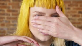 Stående av den unga kvinnan med gult hår som ser kameran och flyttning hennes händer runt om henne framsida, bakgrund för tegelst lager videofilmer