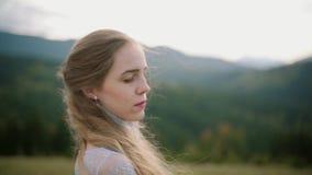 Stående av den unga kvinnan med hår som blåser i vind som ser solnedgång i berg långsam rörelse stock video