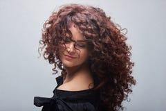 Stående av den unga kvinnan med lockigt hår för trend arkivbild