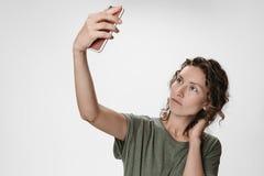Stående av den unga kvinnan med lockigt hår som har video-appellen som rymmer den smarta telefonen arkivfoton