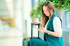 Stående av den unga kvinnan med smartphonen i internationell flygplats Flygbolagpassagerare i vänta på för flygplatsvardagsrum Royaltyfri Foto