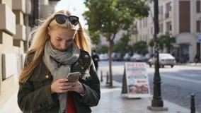 Stående av den unga kvinnan som använder telefonen, utomhus Allvarlig härlig maskinskrivning för ung kvinna på telefonen under so stock video