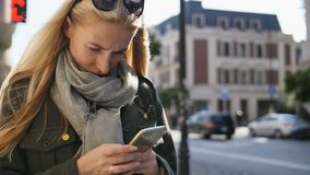 Stående av den unga kvinnan som använder telefonen, utomhus Allvarlig härlig maskinskrivning för ung kvinna på telefonen under so arkivfilmer