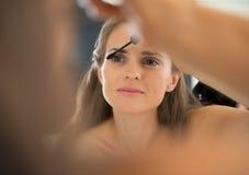 Stående av den unga kvinnan som applicerar mascara Royaltyfri Foto