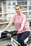 Stående av den unga kvinnan som cyklar bredvid floden i stads- inställning Arkivbild