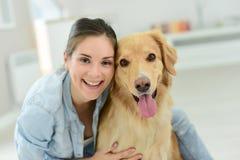 Stående av den unga kvinnan som daltar hennes hund Royaltyfria Bilder