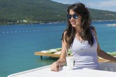 Stående av den unga kvinnan som dricker fruktsaft på stranden Arkivbild