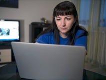 Stående av den unga kvinnan som hemma arbetar på bärbara datorn i aftonen arkivfoton