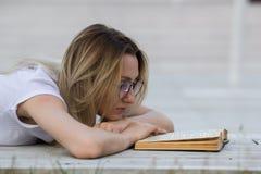 Stående av den unga kvinnan som läser en bok som ligger på bänken i parkera Royaltyfria Foton